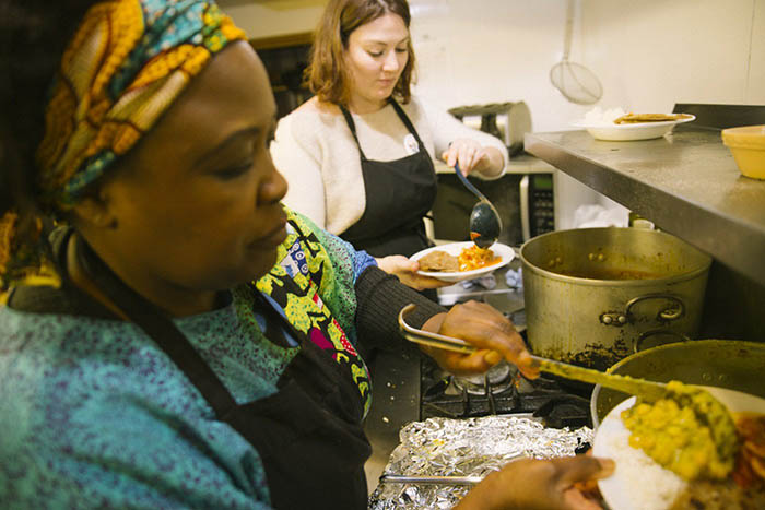 Two women plating up food in a kitchen at one of the 2017 Africa in Motion dine and view events
