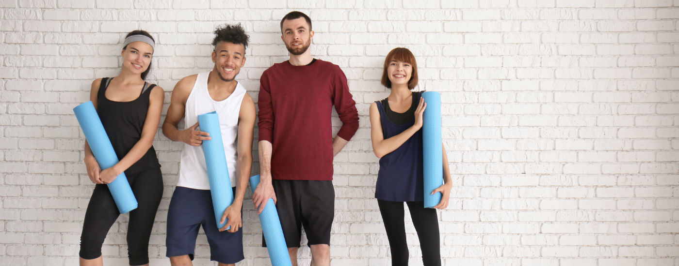Group of gym members standing together, holding yoga mats