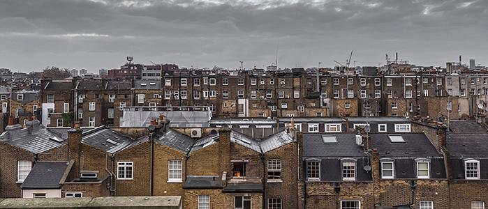 Rooftop view of old houses in London with grey sky and clouds. 700 pixels