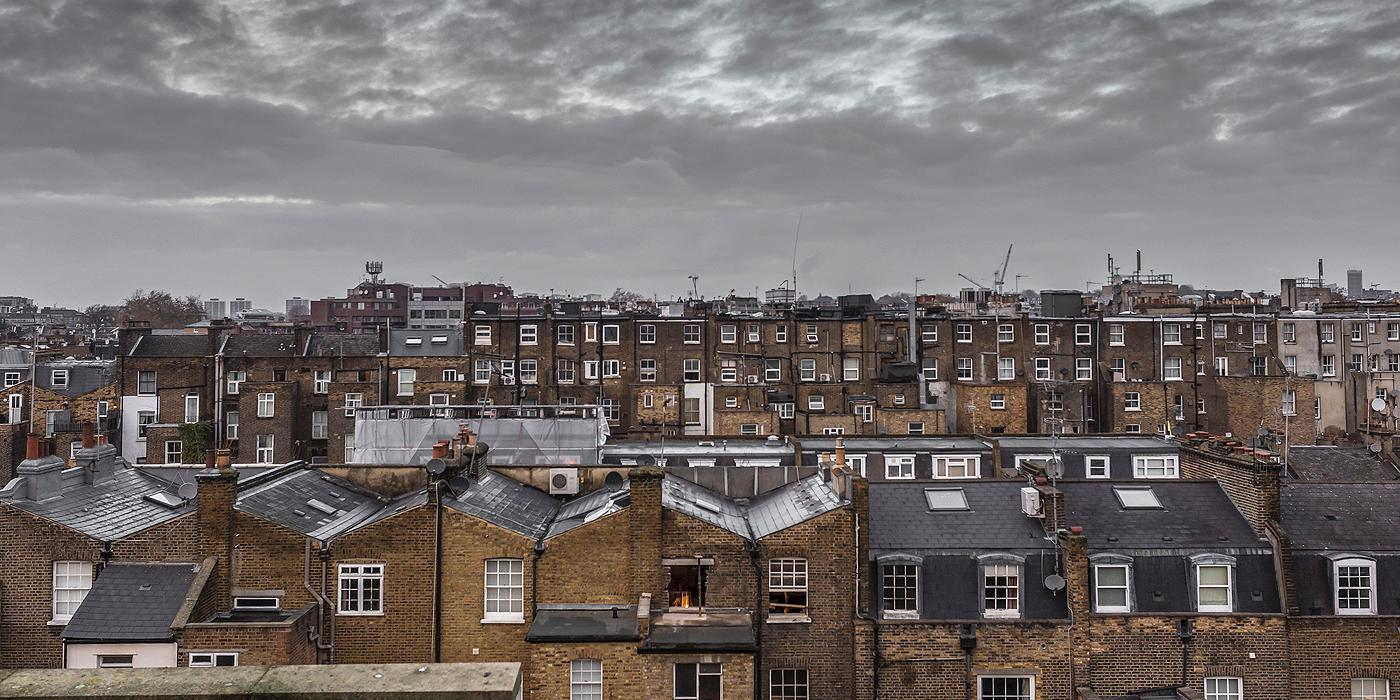 Rooftop view of old houses in London with grey sky and clouds. 1400 pixels