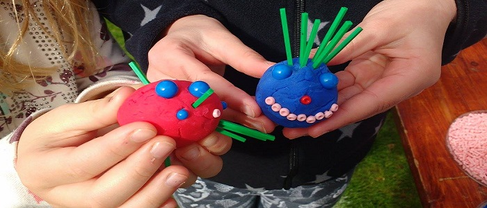 Image of hands holding model viruses made with airdough and pegs