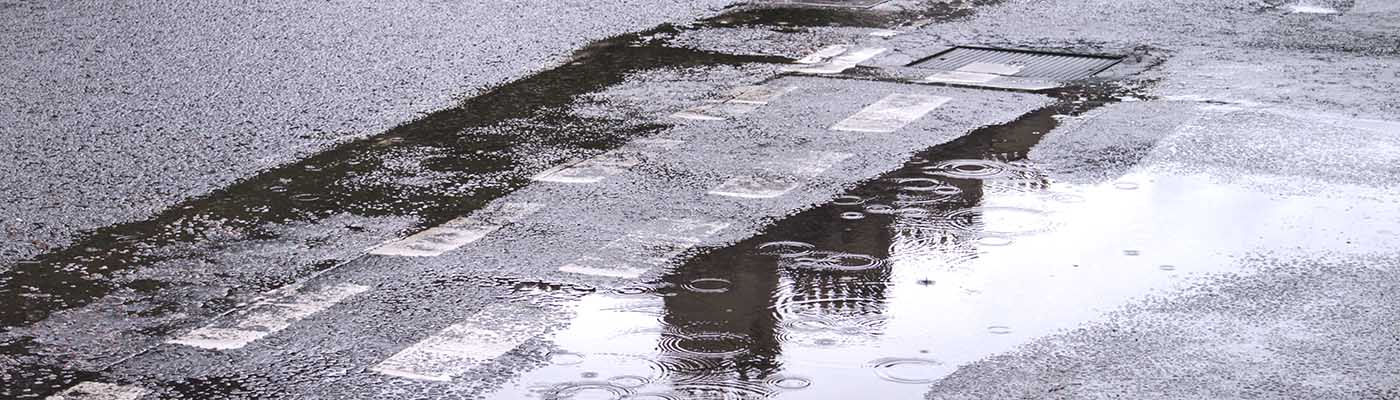 rain falling on a puddle over road markings