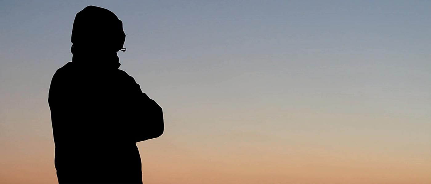 Silhouette of a person looking at a sunset