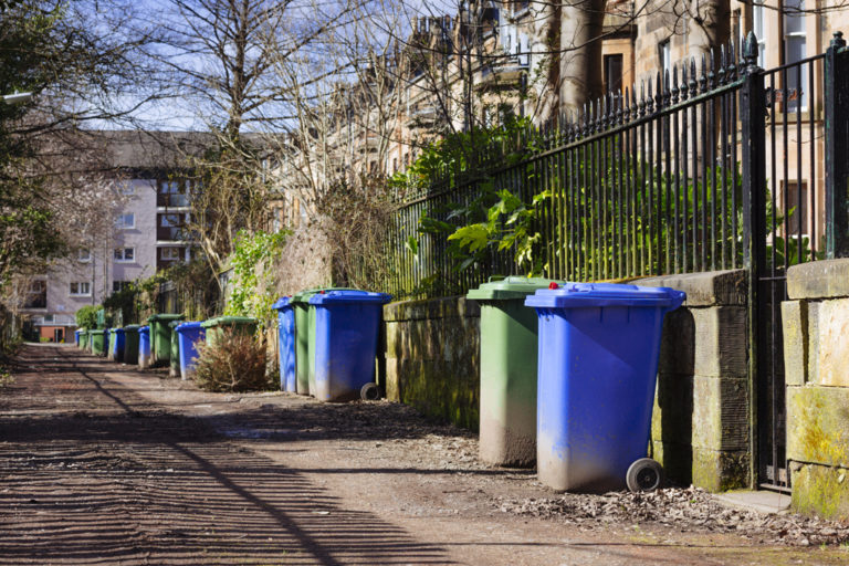 Wheelie bins (blue for recycling, green for general refuse) lined up for collection in a Glasgow alley. 768x512px