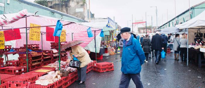 Glasgow, people walking around the historic Barras Market Place flea market. 768x512px
