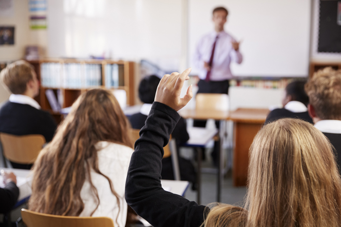 View from behind of classroom with a female pupil holding hand up to ask a question, 700px
