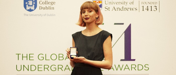 Undergraduate Awards Izzy Howlett with medal at ceremony in Dublin 700 x 300