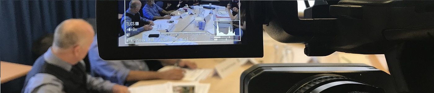 View from behind a camera filming a meeting