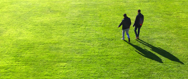 Photo of two men walking across an expanse of grass