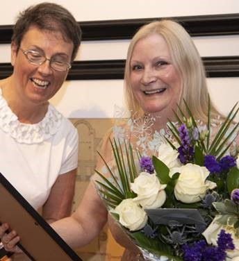 Photo of Professor Anna Cooper being presented with flowers by Professor Jill Pell on the occasion of her retirement