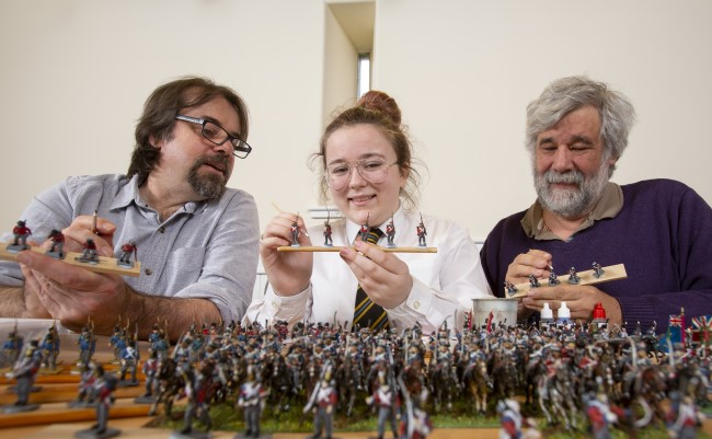Left to Right: Professor Tony Pollard, Professor of Conflict History and Archaeology at the University of Glasgow; Lucy Wallace, S3 Pupil, Clydebank High School and John Hamilton, Volunteer for the Model Making Group at Erskine, helping to paint some of the 22,000 28mm figures to be used in Great Game: Waterloo Replayed which will be  the biggest ever historical table top war game.