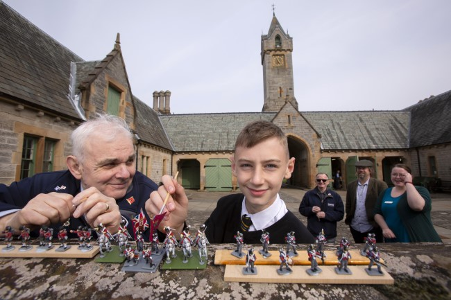 Robert McCreadie (right) from Dumbarton, a Royal Navy veteran & S3 pupil Calan Mulgrew, Clydebank High School inspecting some of the 28mm figures which will take part in The Great Game: Waterloo Replaye. Background (l to r)  – Steve Wyllie, an Army veteran i; Professor Tony Pollard & Evonne McCord, Activities Co-ordinator at the Erskine Activities Centre