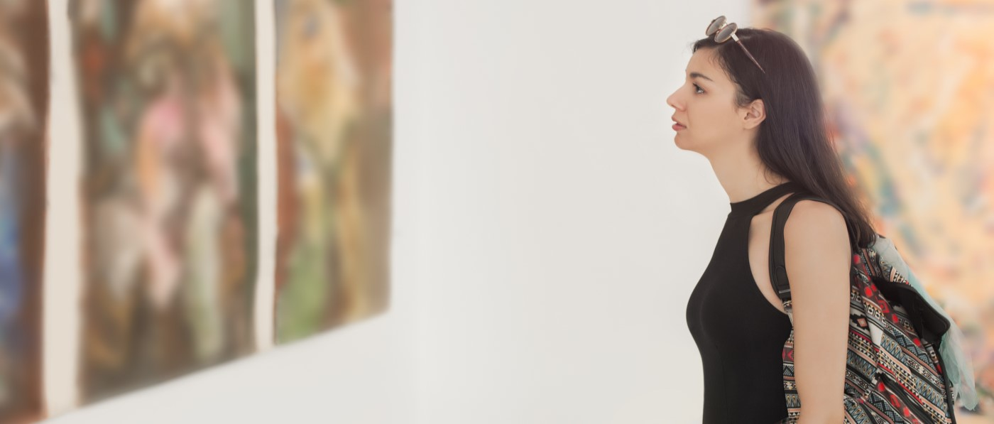 Photo of woman in gallery looking at painting