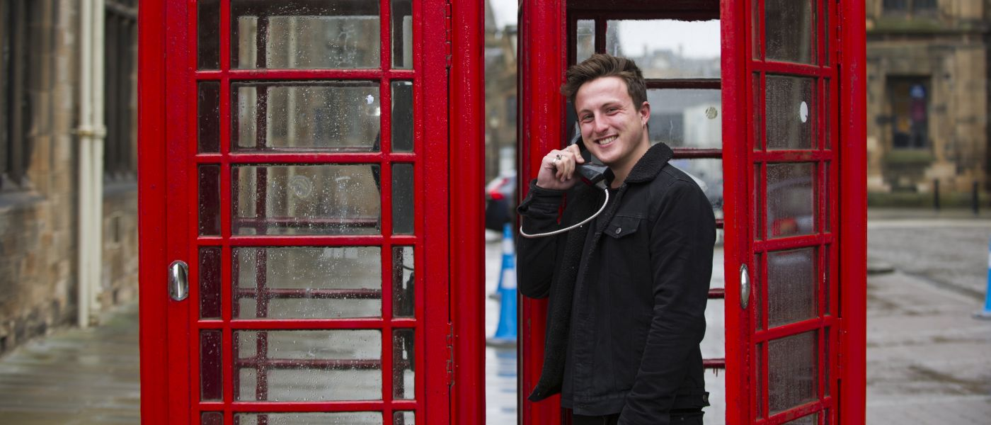 One student caller making a phone call outside the main gates on the red pay phone boxes