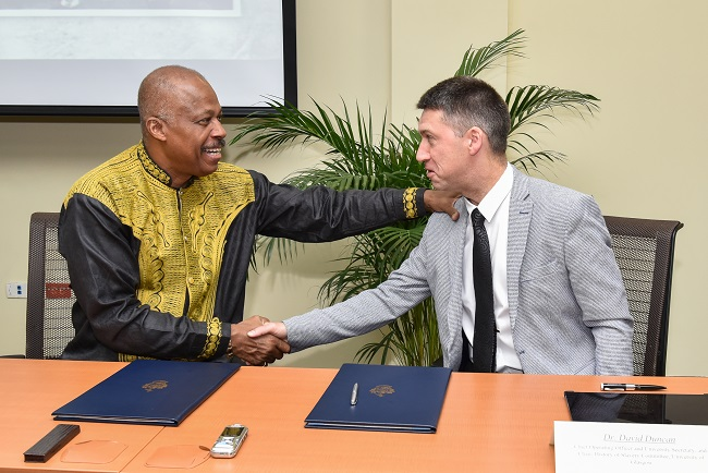 Professor Sir Hilary Beckles (seated left), Vice-Chancellor of The University of the West Indies (The UWI) and Dr. David Duncan, Chief Operating Officer & University Secretary, University of Glasgow, shake hands following the signing of the Memorandum of Understanding at The UWI Regional Headquarters, Kingston, Jamaica on July 31, 2019, to partner in a reparations strategy