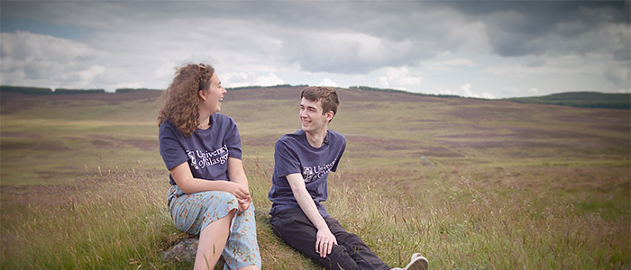 A female and male student wearing University of Glasgow t-shirts sitting in a field with hills behind them