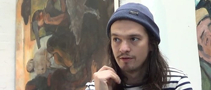 headshot photo of a young ethnically-ambiguous man with long hair, a blue beanie and facial hair in front of a painting in browns and beiges