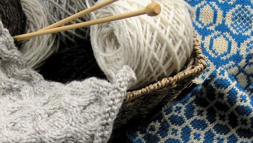 Close up image of yarn, knitting needles and knitting in progress