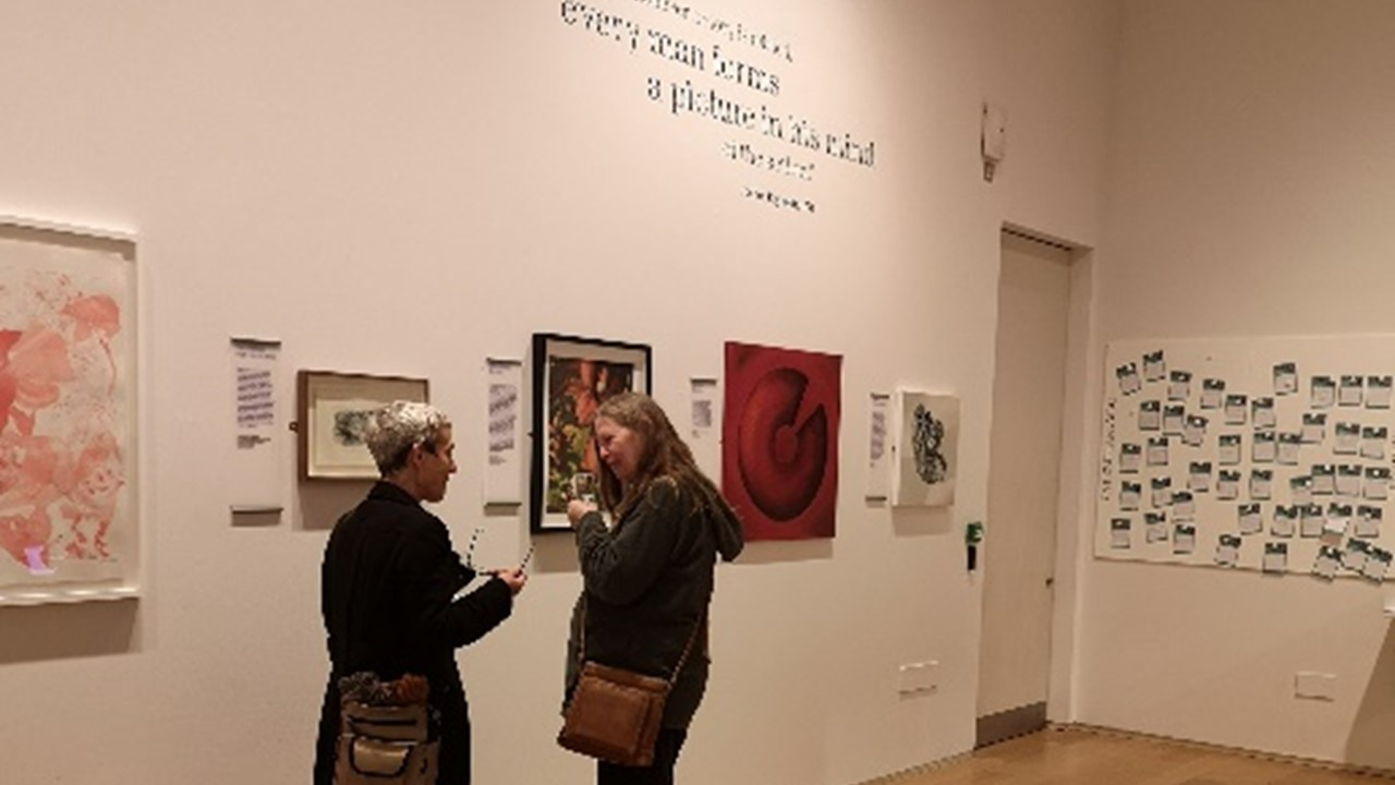 photo of two white women deep in conversation, against a white wall of a gallery full of artwork that we can see in the online exhbition, as well as description writing in black on the wall. On the back wall in the background, comment cards are attached to a felt panel.