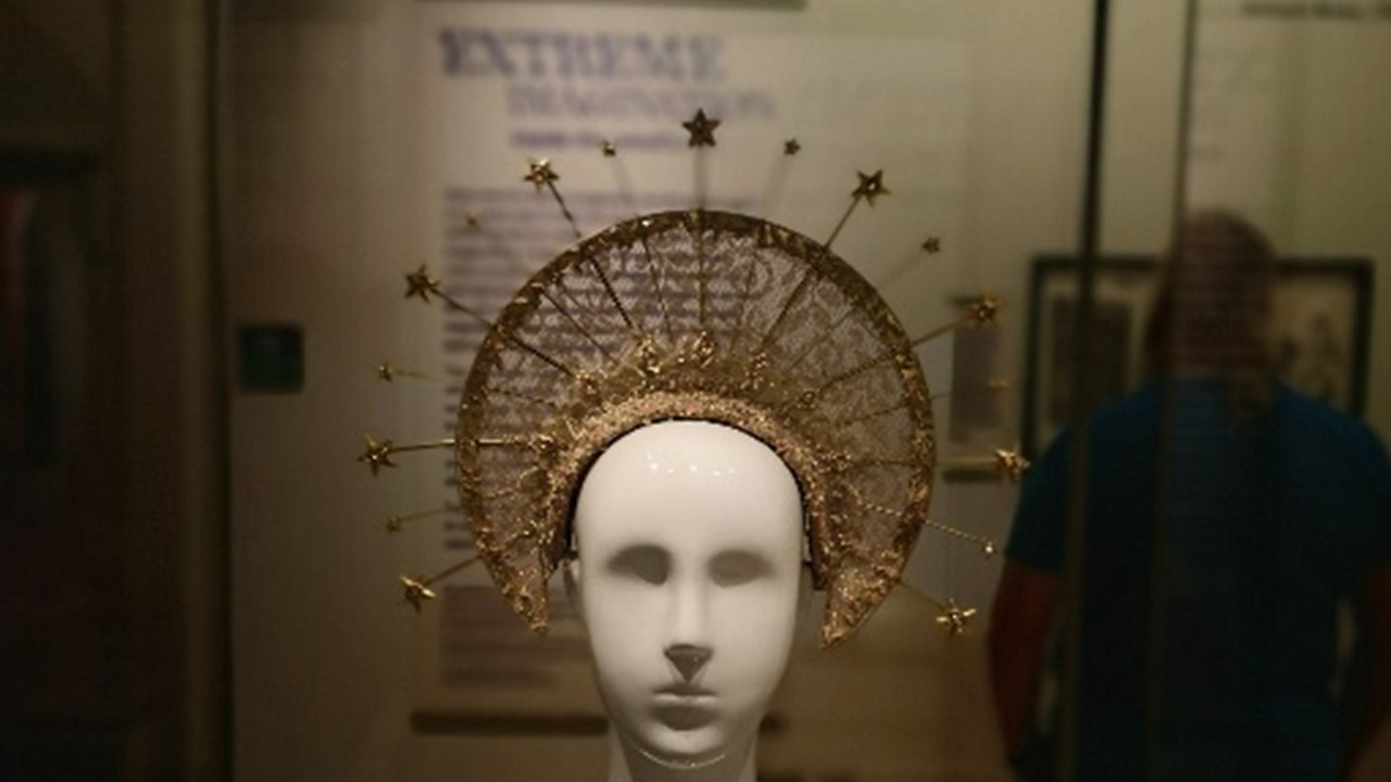 semi-dark photograph of one of the exhibits in the Extreme Imagination exhibition presented as a white mannequin bust with an elaborate golden crown that looks like a halo with golden spikes and stars offset from the edge of the halo. In the background, partly obscured, exhibition explanatory black text on a white wall