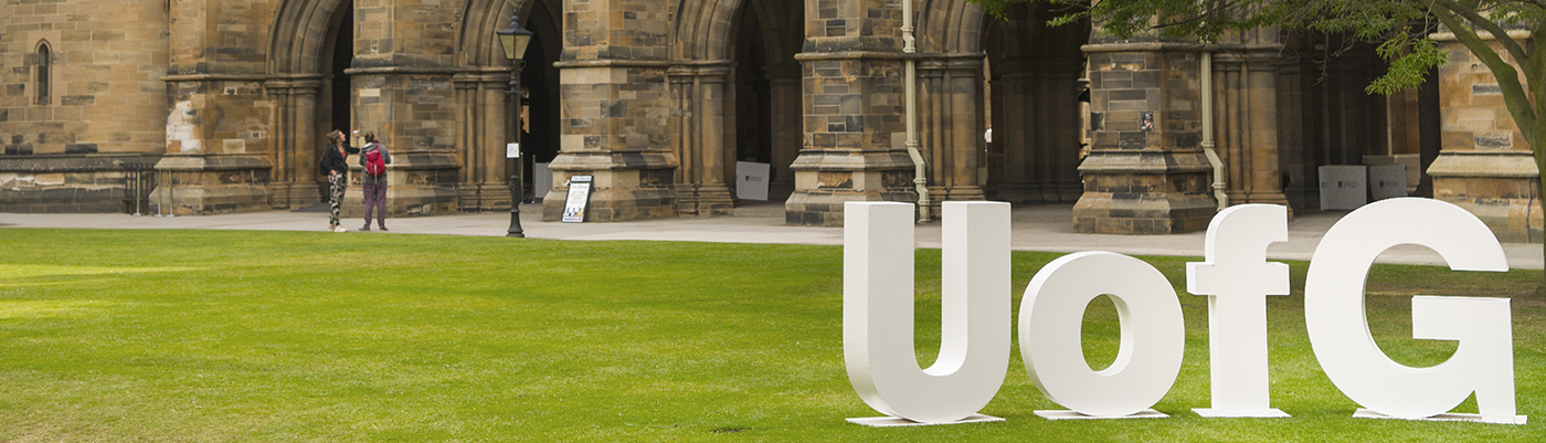 UofG letters in the West Quadrangle of the Main Building with the cloisters in the background