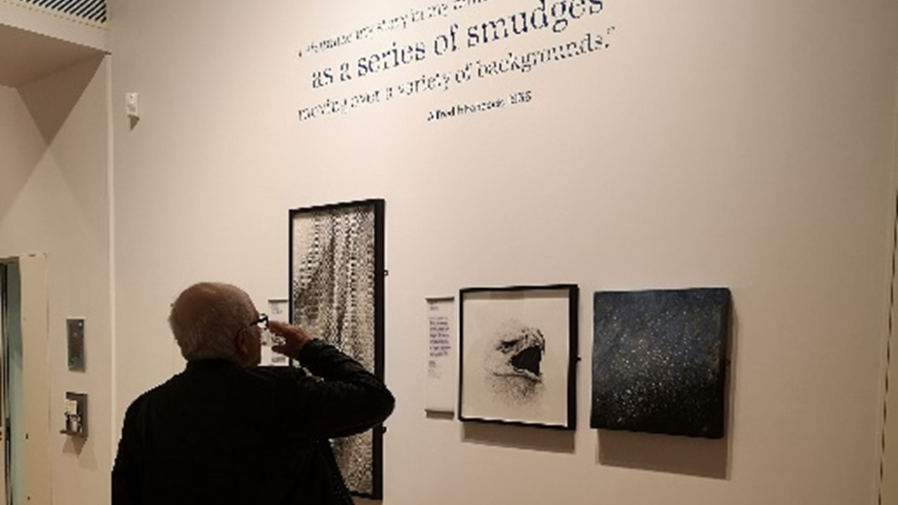 a photograph of the interior of the exhibition with a figure with the back towards the viewer, raising his hand as to shield his eyes or take a drink. In background two images that can be viewed in the online exhbition (a black and white textile and a blue sparkling non-figurative painting) as well as the charcoal drawing of an eagle hang framed on a wall.