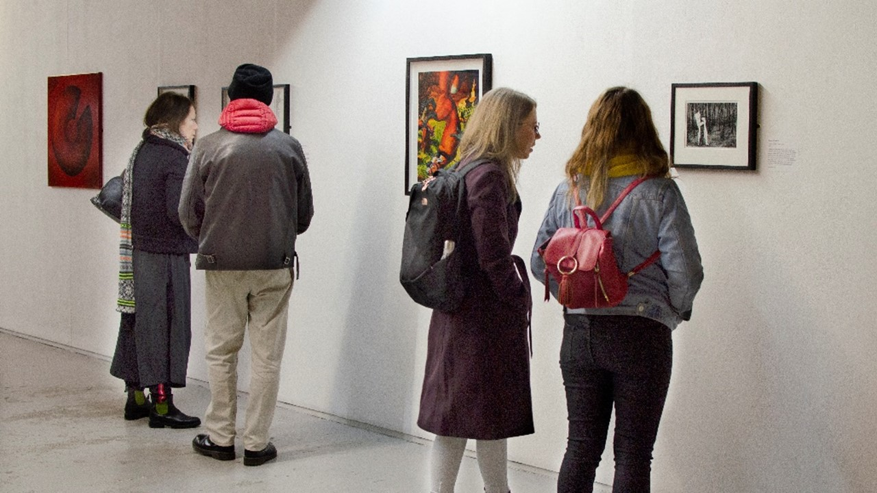 long panoramic view of the inside of the exhibition with four figures of different genders in front of white walls with artwork framed and hung up.