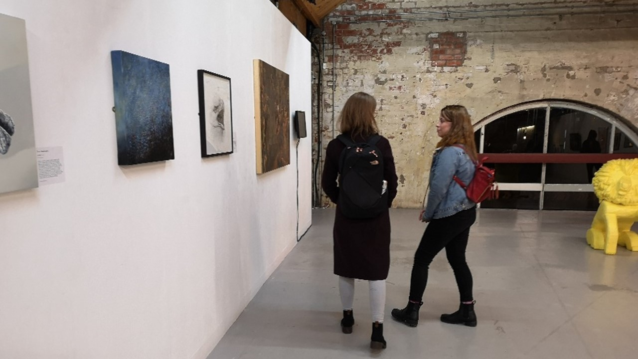 long panoramic view of the inside of an exhibitoon space with one long white wall with artwork framed and hung and a back wall made out of stone with a vaulted window framed by darker blocks of stone. Two people talk to each other, partially facing the artwork hung on the wall
