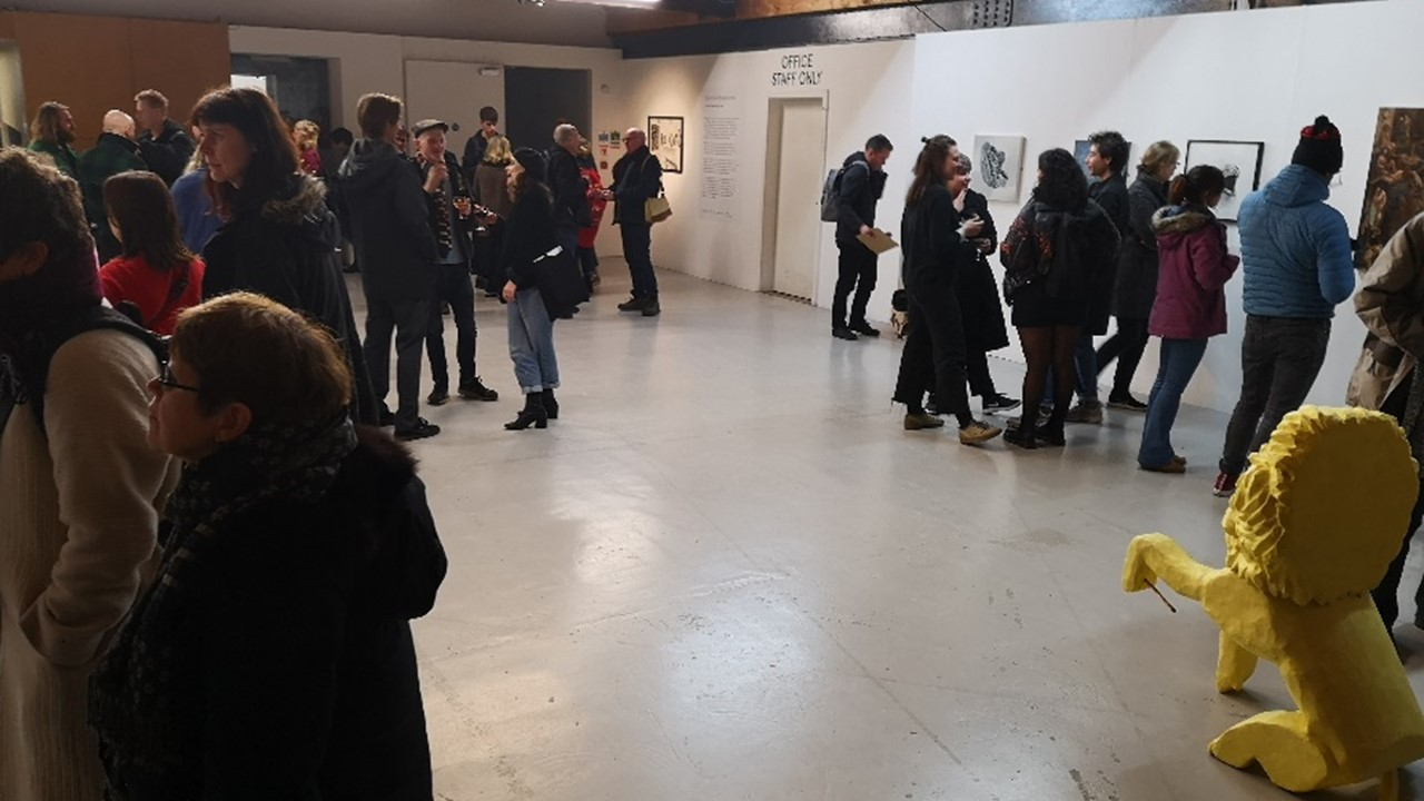 wide image of an unconventional gallery space with white as well as stone walls, with a lot of people in small groups looking at pictures on the wall and discussing. In the foreground we can see the yellow cast lion