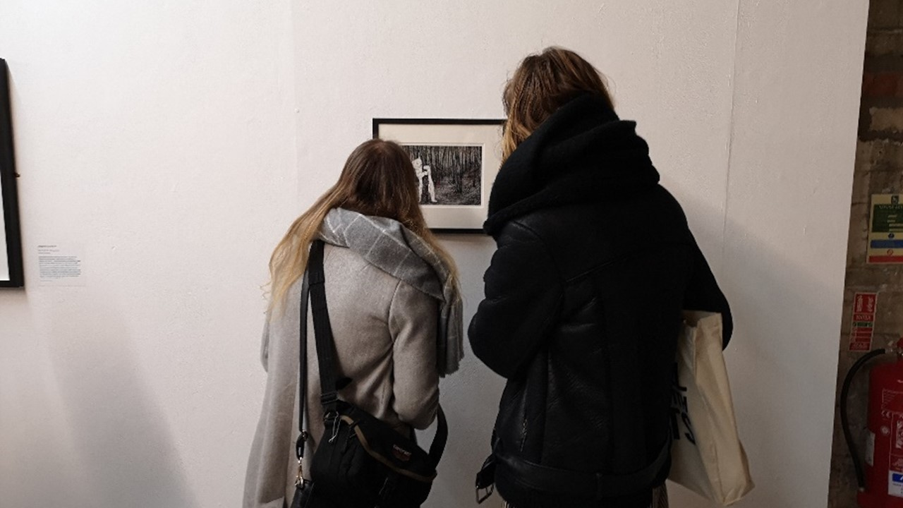 photo of two people in puffy jackets gathered close around an artwork framed and hung on a white wall. The artwork is a drawing print of a polar bear in the woods.