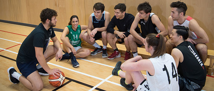 Students from the Basketball team sitting in a group in the sports hall