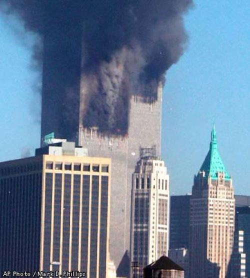 News photograph from the 11th of September 2001 terrorist attack on the World Trade Centre towers: tall skyscrapers from foreground are dwarfed by a much taller block of 2 skyscrapers emitting smoke from two different points. In the fluffy rolling swathes of grey smoke, a satanic face with angular chin and nose, and narrow eyes, can be made out.