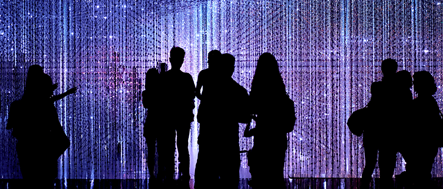 People in a dark room with sparkle lighting effect.