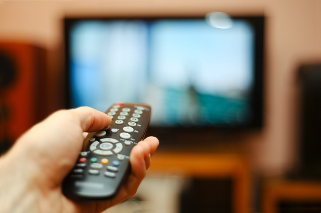 A person holding the remote in front of the TV
