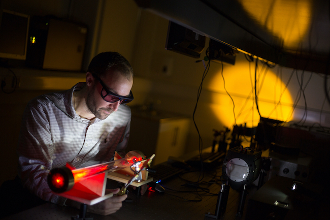 Prof Daniele Faccio examines an optical experiment on a lab bench while wearing a pair of safety glasses.