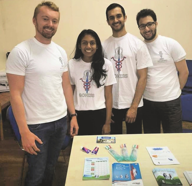 Photograph of four dental students with their stall at a foodbank
