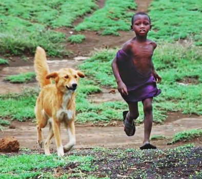 Small boy running with dog. Credit Katie Hampson