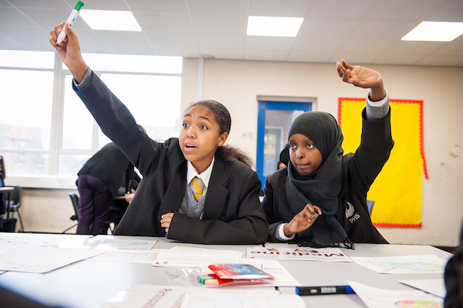 Two high school pupils raise their hands to answer a question in class. Photo courtesy of IntoUniversity