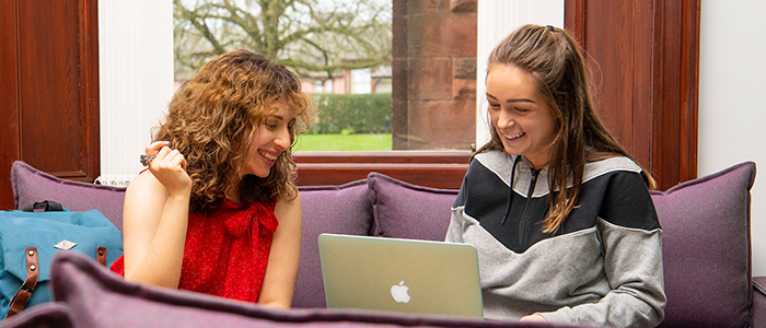 Two students laughing and looking at a laptop in the Rutherford McCowan cafe