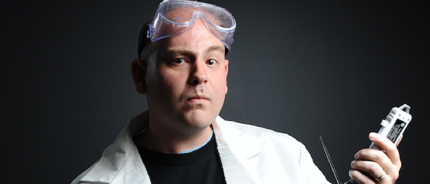 Photo of Dr Jeff Dalton in a white lab coat posing with a piece of technological equipment