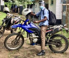 A member of the Coverso project study team sat on a motorbike