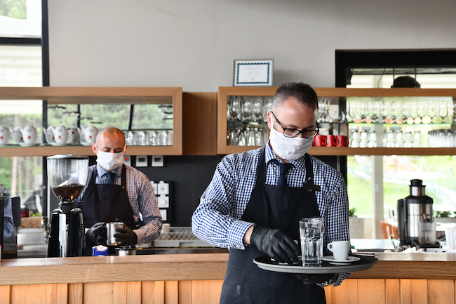 Two masked and gloved waiters work inside a restaurant during the COVID-19 pandemic